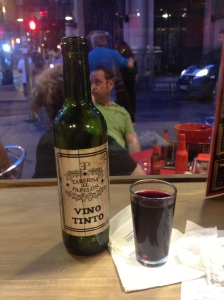 Tiny bottle of wine with a glass that is probably highly appropriate to Spanish culture.