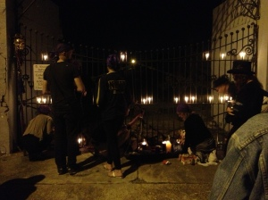 Laying candles along the closed cemetery gates.
