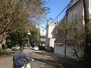 Vincenzo walking the broken down moped through the streets of the Garden District.